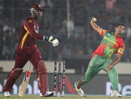 Bangladesh's Ziaur Rahman bowls as West Indies' Marlon Samuels looks on during their ICC Twenty20 World Cup match at the Sher-E-Bangla National Cricket Stadium in Dhaka March 25, 2014. REUTERS/Andrew Biraj