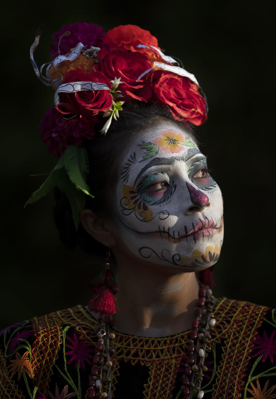 "Gabriela Ruiz is dressed as a ""Catrina"" to perform in a play promoting the upcoming Day of the Dead holiday, at the Nativita pier in the Xochimilco borough of Mexico City, Friday, Oct. 23, 2020. The iconic figures of skeletons with elegant wide-brimmed hats better known as Catrinas were created as satirical prints by Mexican artist Jose Guadalupe Posada sometime between 1910 and his death in 1913. (AP Photo/Marco Ugarte)"
