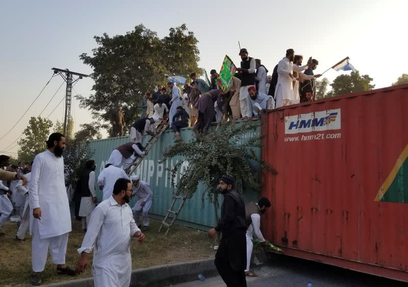 People climb over shipping containers as they try to go towards the French Embassy during a protest against the cartoon publications of Prophet Mohammad in France, in Islamabad