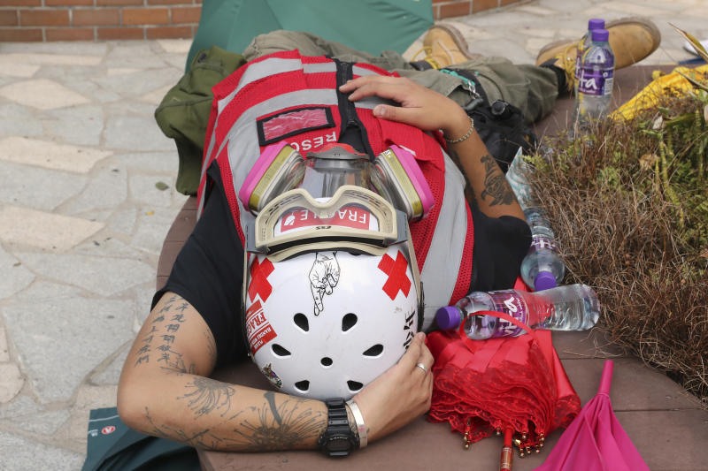 A volunteer first aid medic rests at the Hong Kong Polytechnic University in Hong Kong, Thursday, Nov. 14, 2019. University students from mainland China and Taiwan are fleeing Hong Kong, while those from three Scandinavian countries have been moved or urged to leave as college campuses become the latest battleground in the city's 5-month-long anti-government unrest. (AP Photo/Ng Han Guan)