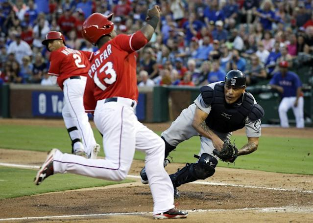 Texas Rangers' Jurickson Profar sprints toward the plate as Seattle Mariners catcher Henry Blanco attempts the tag in the second inning of a baseball game, Saturday, Aug. 17, 2013, in Arlington, Texas. Profar scored on the bunt single by Leonys Martin, rear. (AP Photo/Tony Gutierrez)