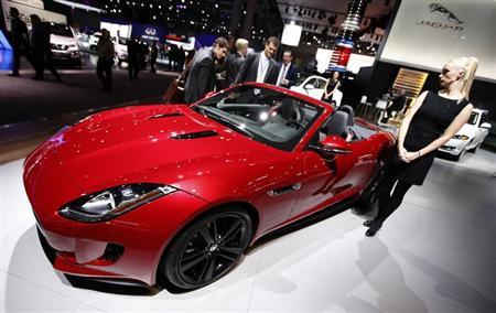 A model stands next to a Jaguar F Type S convertible model, winner of the 2013 World Car Awards World Car Design of the Year during a press preview at the 2013 New York International Auto Show
