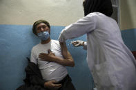 """A man receives the Sinopharm COVID-19 vaccine at a vaccination center, in Kabul, Afghanistan, Wednesday, June 16, 2021. In Afghanistan, where a surge threatens to overwhelm a war-battered health system, 700,000 doses donated by China arrived over the weekend, and within hours, """"people were fighting with each other to get to the front of the line,"""" said Health Ministry spokesman Dr. Ghulam Dastigir Nazari. (AP Photo/Rahmat Gul)"""