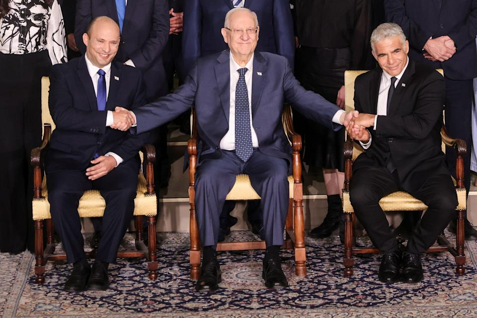 Israel's President Reuven Rivlin between Prime Minister Naftali Bennett and Foreign Minister Yair Lapid as they pose for a group photo with ministers of the new Israeli government (Reuters)