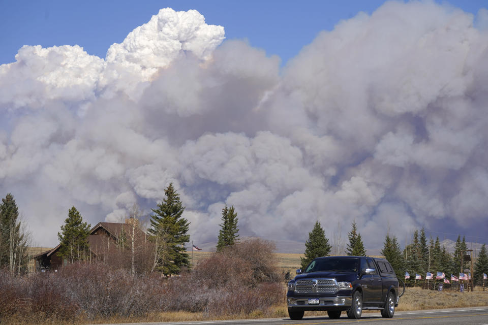 Smoke rises from mountain ridges as a motorist heads eastbound on Highway 34 while a wildfire burns Thursday, Oct. 22, 2020, near Granby, Colo. (AP Photo/David Zalubowski)