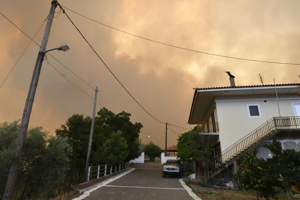 A wildfire approaches a village near Pyrgos town, western Greece, Thursday, Aug. 5, 2021. Wildfires rekindled outside Athens and forced more evacuations around southern Greece Thursday as weather conditions worsened and firefighters in a round-the-clock battle stopped the flames just outside the birthplace of the ancient Olympics. (Giannis Spyrounis/ilialive.gr via AP)