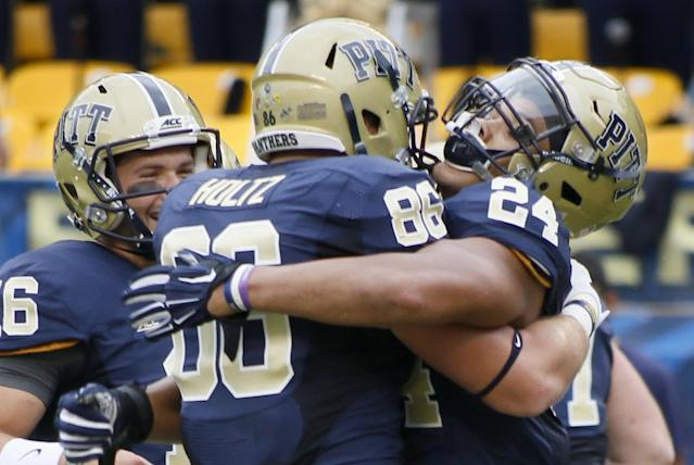 Pittsburgh running back James Conner (24), right, celebrates with teammates tight end J.P. Holtz (86) and quarterback Chad Voytik (16) after scoring in the first quarter of the NCAA football game against the Delaware on Saturday, Aug. 30, 2014 in Pittsburgh. (AP Photo/Keith Srakocic)