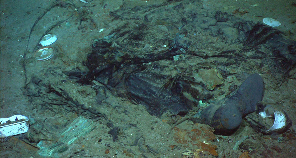 This 2004 photo provided by the Institute for Exploration, Center for Archaeological Oceanography/University of Rhode Island/NOAA Office of Ocean Exploration, shows the remains of a coat and boots in the mud on the sea bed near the Titanic's stern. Fallout from the coronavirus pandemic is threatening a company's plans to retrieve and exhibit the radio that had broadcast distress calls from the sinking vessel, according to a court filing made by the firm on Monday, Jan. 11, 2021. (Institute for Exploration, Center for Archaeological Oceanography/University of Rhode Island/NOAA Office of Ocean Exploration)