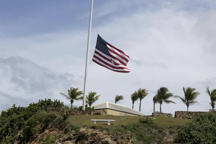 A U.S. flag flies at half staff on Little St. James Island, in the U. S. Virgin Islands, a property owned by Jeffrey Epstein, Wednesday, Aug. 14, 2019. Many in nearby St. Thomas are debating what should be done with the structures and even the islands themselves, even though it is unclear who would inherit Little St. James Island and neighboring Great St. James Island. (AP Photo/Gabriel Lopez Albarran)