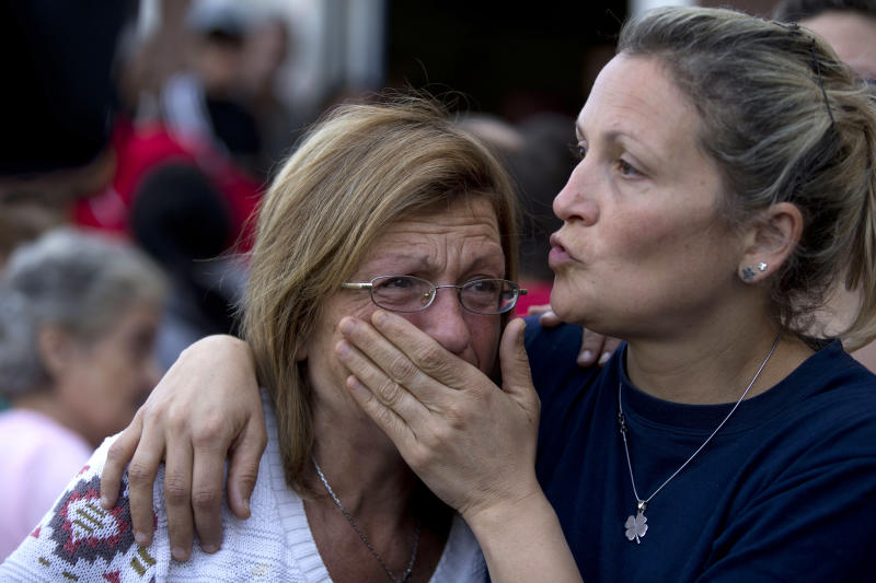 A woman is comforted by a relative outside a club where the Red Cross set up a center to people affected by flooding in La Plata, in Argentina's Buenos Aires province, Thursday, April 4, 2013. Buenos Aires Gov. Daniel Scioli says 49 people died in this flooded capital of Argentina's largest province as torrential rains swamped entire neighborhoods, washing away cars and flooding some houses to their rooftops. The overall death toll is now 55, and more than 20 people are missing. (AP Photo/Natacha Pisarenko)
