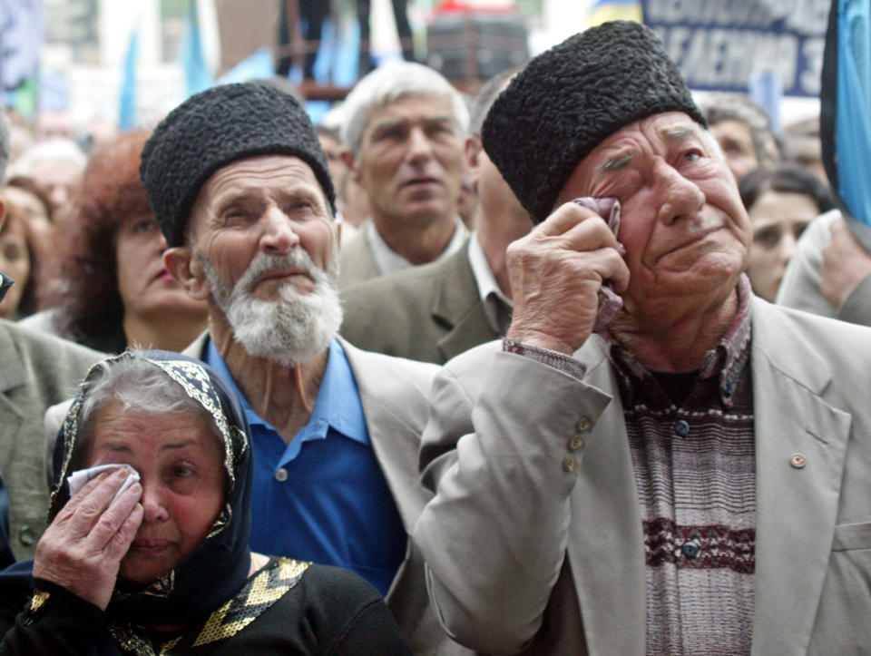 FILE - In this May 18, 2004 file photo, Crimean Tatars wipe away their tears at a mourning rally during the 60th anniversary of deportation of ethnic Tatars under Soviet dictator Josef Stalin, in the Crimean capital of Simferopol, Ukraine. The fate of Crimean Tatars is one of the top issues at the inaugural meeting of the Crimean Platform on Monday Aug. 23, 2021, an international summit called by Ukraine to build up pressure on Russia over the annexation that has been denounced as illegal by most of the world. (AP Photo/Efrem Lukatsky, File)