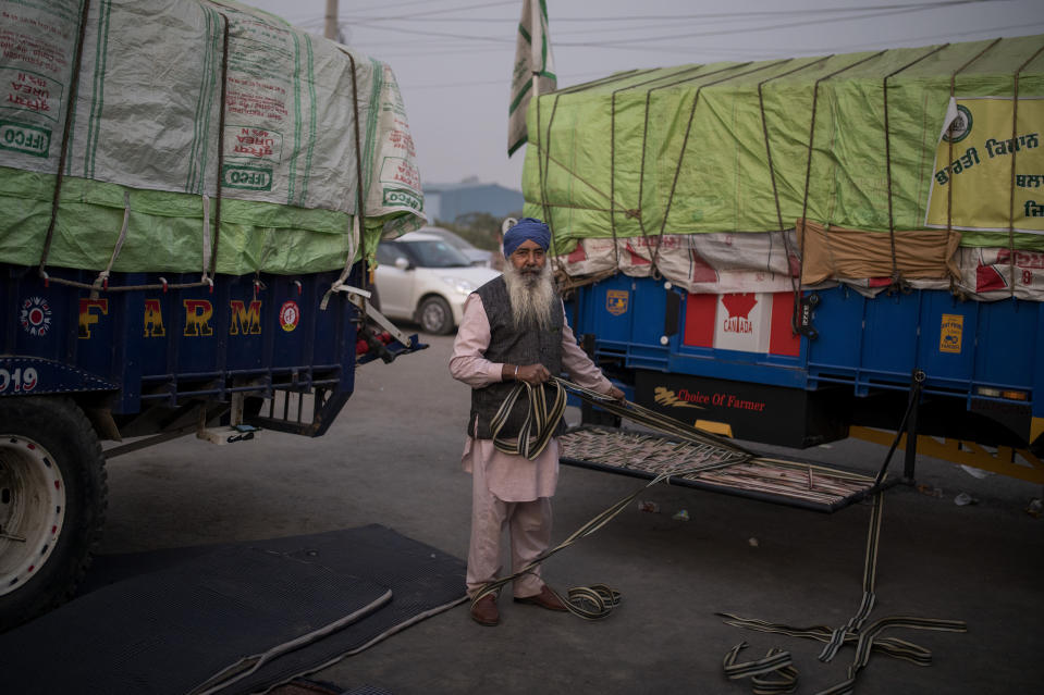 Farmer Satnam Singh, 67, repairs his makeshift cot attached to his tractor trailer parked on a highway during a protest, in the Delhi-Haryana state border, India, Wednesday, Dec. 2, 2020. Instead of cars, the normally busy highway that connects most northern Indian towns to the capital is filled with tens of thousands of protesting farmers, many wearing colorful turbans. The farmers are protesting new laws they say will result in their exploitation by corporations, eventually rendering them landless. (AP Photo/Altaf Qadri)