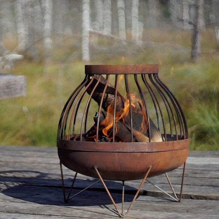 """If you're looking for unique outdoor fire pit ideas, how about this contemporary beauty fit for any patio centerpiece? It's made of weather-resistant carbon steel that'll age beautifully, and it gets extra points for durability. $369, Wayfair. <a href=""""https://www.wayfair.com/outdoor/pdp/ebern-designs-rector-solid-steel-wood-burning-fire-pit-w002669463.html"""" rel=""""nofollow noopener"""" target=""""_blank"""" data-ylk=""""slk:Get it now!"""" class=""""link rapid-noclick-resp"""">Get it now!</a>"""