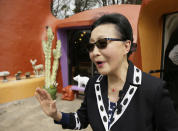 FILE - In this Thursday, April 11, 2019, file photo, Florence Fang talks with reporters after a news conference outside her Flintstone House in Hillsborough, Calif. The owner of a San Francisco Bay Area home adorned with fanciful Flintstones characters is filing her counterclaim against the city that is trying to force her to remove the unpermitted installations. Technically, the owner of the Flintstones house settled a lawsuit with the town of Hillsborough. But the agreement will allow Fred and his friends to remain. (AP Photo/Eric Risberg, File)