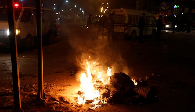 <p>Police vehicles stop in front of burning tires set up by protesters during demonstrations against rising prices and tax increases, in Tunis, Tunisia, Jan. 8, 2018. (Photo: Zoubeir Souissi/Reuters) </p>