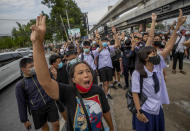 Pro-democracy protesters flash three-fingered salute during a demonstration at Kaset intersection, suburbs of Bangkok, Thailand, Monday, Oct. 19, 2020. Thailand's embattled Prime Minister Prayuth Chan-ocha said Monday that there were no plans to extend a state of emergency outside the capital, even as student-led protests calling for him to leave office spread around the country. (AP Photo/Sakchai Lalit)