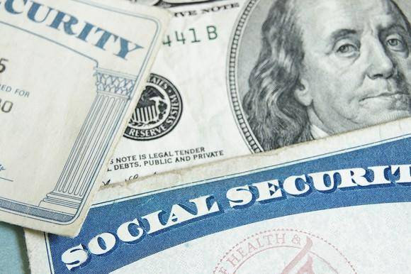 Two Social Security cards next to a $100 bill on a flat surface.
