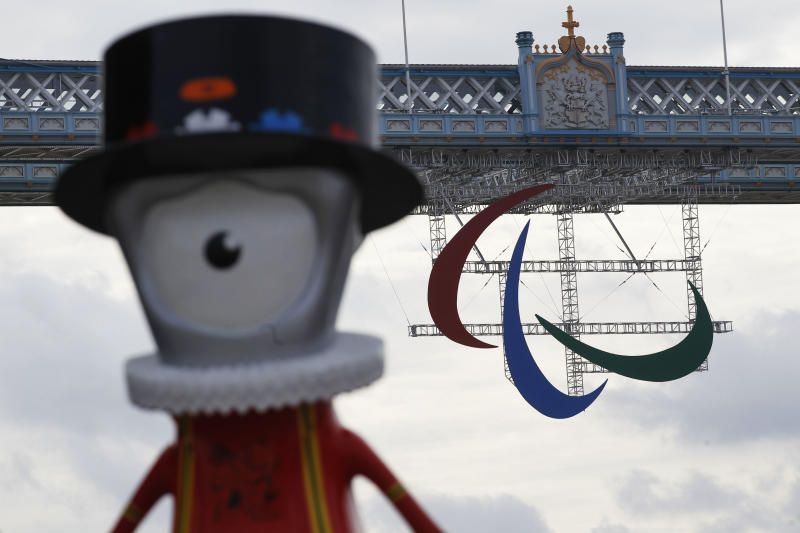 A Paralympic Games symbol hangs from Tower Bridge in London, with a Beefeater games mascot Mandeville, in foregroud, Friday, Aug. 24, 2012. The London 2012 Paralympic Games starts on Wednesday, Aug. 29. (AP Photo/Sang Tan)