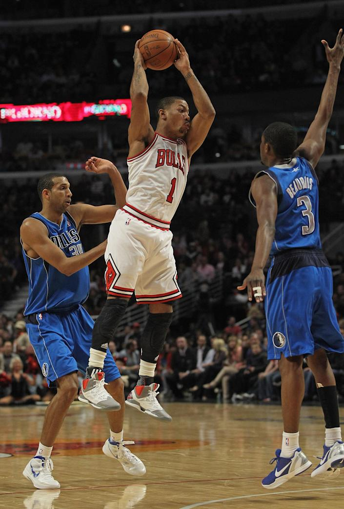 CHICAGO, IL - APRIL 21: Derrick Rose #1 of the Chicago Bulls leaps to pass between Brandon Wright #34 and Rodrigue Beaubois #3 of the Dallas Mavericks at the United Center on April 21, 2012 in Chicago, Illinois. The Bulls defeated the Mavericks 93-83. NOTE TO USER: User expressly acknowledges and agress that, by downloading and/or using this photograph, User is consenting to the terms and conditions of the Getty Images License Agreement. (Photo by Jonathan Daniel/Getty Images)