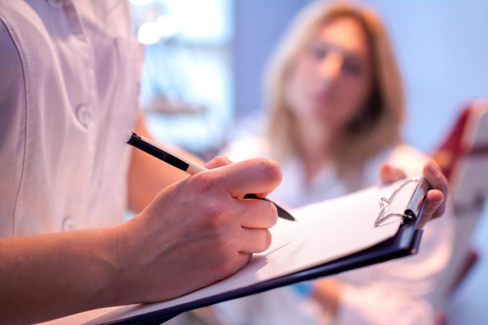 A doctor taking notes on a clipboard while talking to a blurred-out female patient in the background.