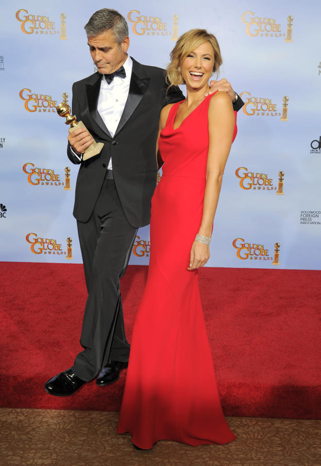"Actor George Clooney, left, poses backstage with the award for Best Actor in a Motion Picture Drama for the film ""The Descendants"" with Stacy Keibler during the 69th Annual Golden Globe Awards Sunday, Jan. 15, 2012, in Los Angeles. (AP Photo/Mark J. Terrill)"