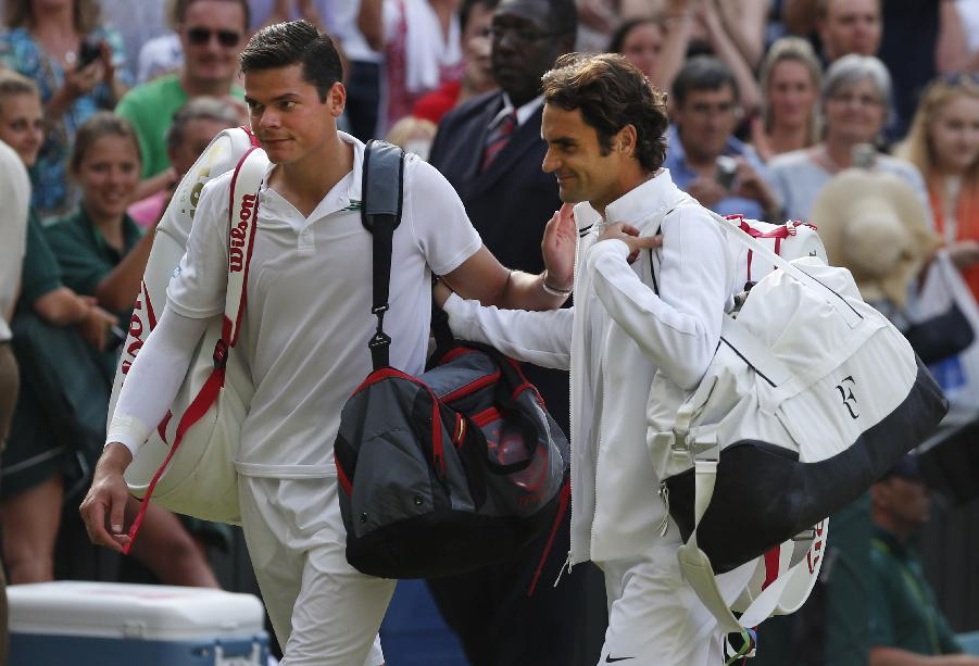 Roger Federer of Switzerland, right, leaves the court with Milos Raonic of Canada after he defeated him in their men's singles semifinal match at the All England Lawn Tennis Championships at Wimbledon, London, Friday, July, 4, 2014.(AP Photo/Ben Curtis)
