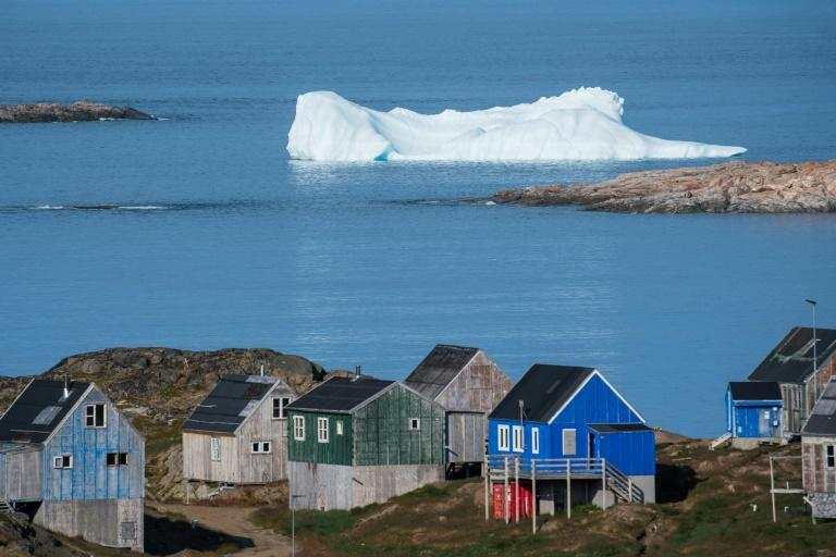 Icebergs float beyong the town of Kulusuk in Greenland. A mining project is reviving debate on the future of this immense Danish Arctic territory, already threatened by global warming but in search of resources for its eventual independence