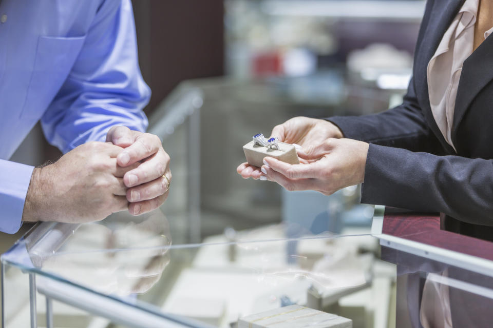 Cropped view of a mature man in his 50s shopping in a jewelry store. The saleswoman is showing him a pair of rings from the display cabinet.