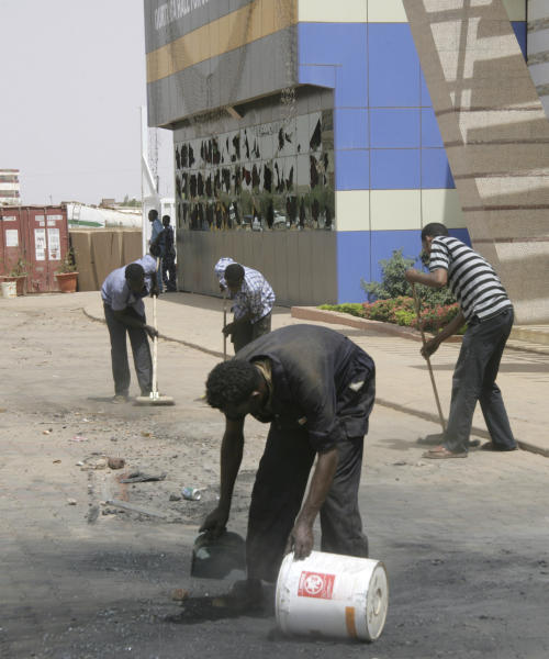 Workers outside the Qurtoba conference hall clean up debris from demonstrations after demonstrations by Sudanese university students and citizens yesterday in the capital Khartoum, Sudan, Sunday, June 24, 2012. Protests were set off by economic austerity measures but marchers are also demanding the ouster of longtime Sudanese President Omar al-Bashir. Sudanese opposition figures say protests have entered their eighth day, as the government vowed to crack down on demonstrators. (AP Photo/Abd Raouf)