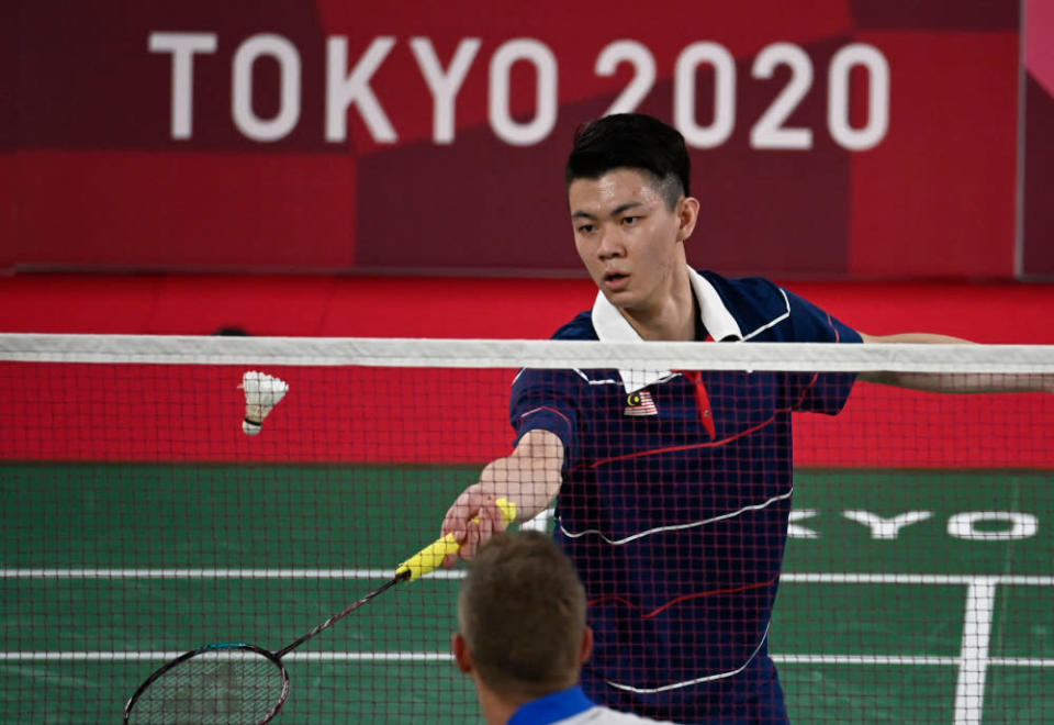 Malaysia's Lee Zii Jia hits a shot to France's Brice Leverdez in their men's singles badminton group stage match during the Tokyo 2020 Olympic Games at the Musashino Forest Sports Plaza in Tokyo July 28, 2021. — AFP pic