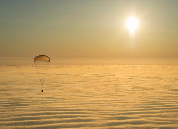 A Russian Soyuz spacecraft carrying three International Space Station crewmembers descends above the clouds to a safe landing in Kazakhstan, March 11, 2014.