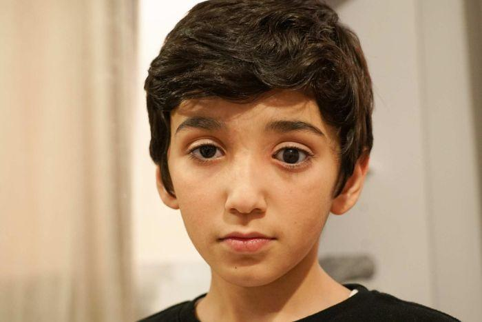 A boy with dark eyes and hair stares at the camera.