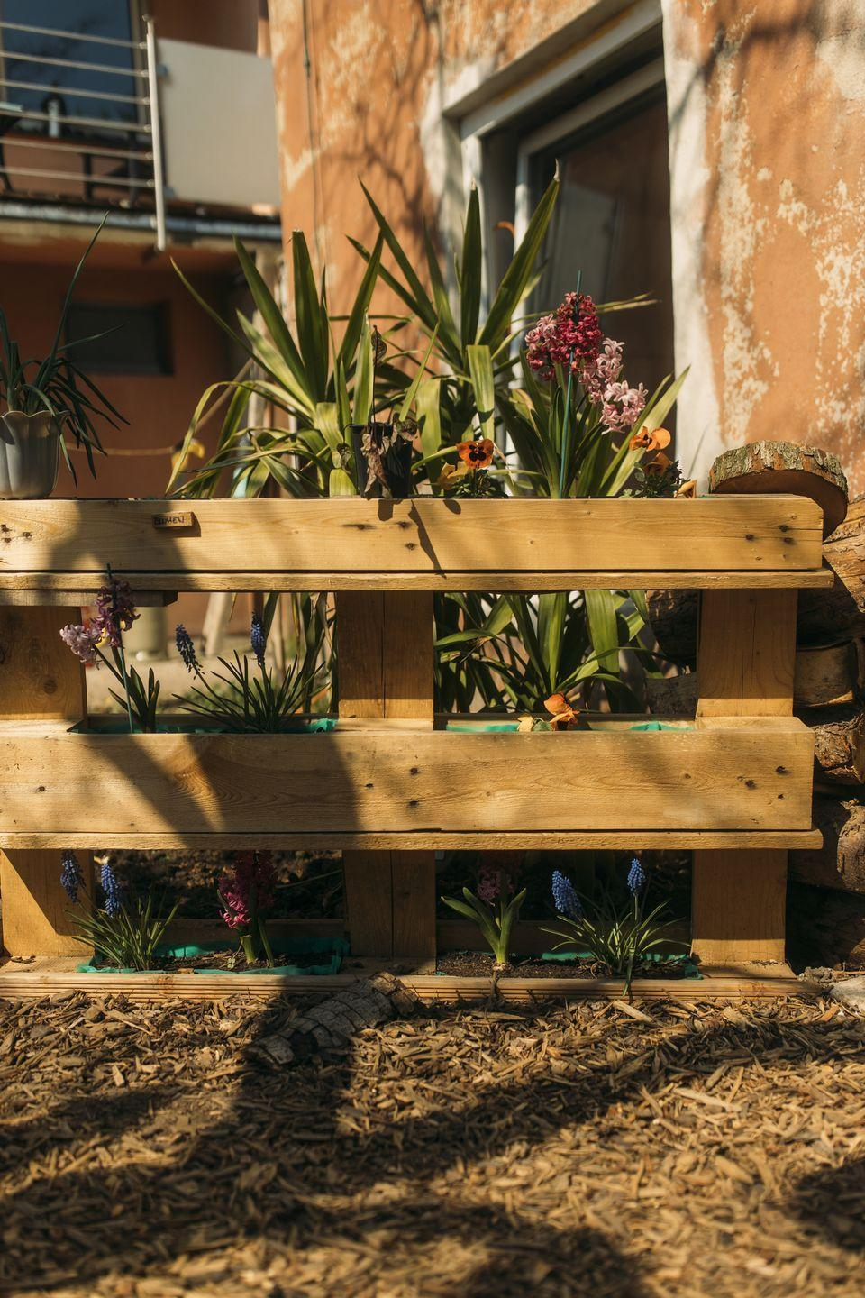 <p>Enhance a wood fence with repurposed crates, which will make draining soil a breeze. </p>