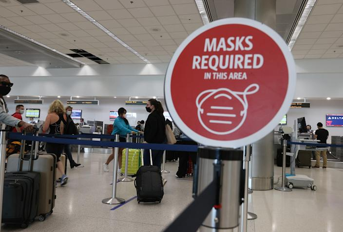A sign reading, 'masks required in this area,' is seen as travelers prepare to check-in for their Delta airlines flight at the Miami International Airport on February 01, 2021 in Miami, Florida (Getty Images)
