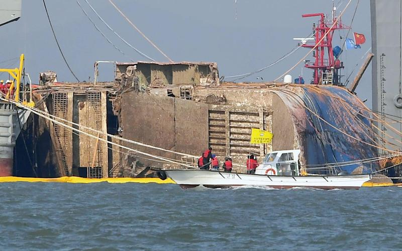 Relatives of missing passengers of the sunken Sewol ferry on a boat, front, watch its salvage operation in waters off Jindo, South Korea - Credit: Kyodo News