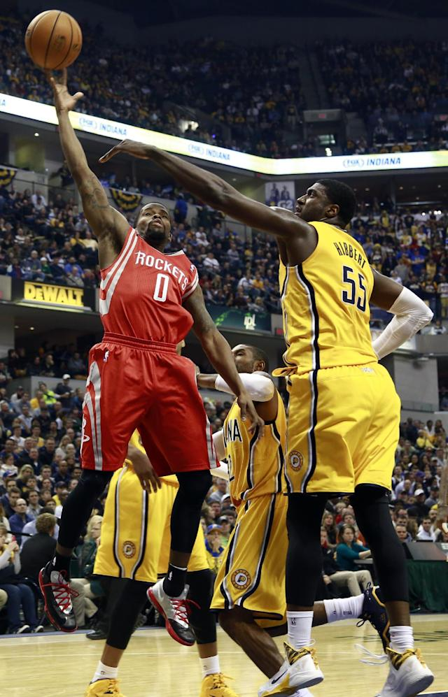 Houston Rockets guard Aaron Brooks (0) shoots while defended by Indiana Pacers center Roy Hibbert (55) in the first half of an NBA basketball game in Indianapolis, Friday, Dec. 20, 2013. (AP Photo/R Brent Smith)