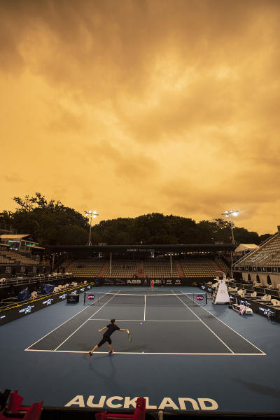 Players practice ahead of the ASB Tennis Classic as the sky in Auckland turns orange as smoke from the Australia wildfires arrives in New Zealand, Sunday, Jan. 5, 2020. Australian Prime Minister Scott Morrison defended his leadership and his government's record on climate change Sunday as milder temperatures brought hope of a respite from wildfires that have ravaged three states, destroying almost 2,000 homes.(Jason Oxenham/New Zealand Herald via AP)
