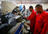 Workers operate a machine at a Bata shoe factory in Abuja