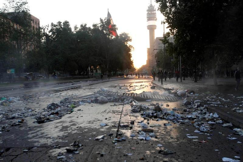 A street with traces of barricades and garbage is seen after a protest against the increase in the subway ticket prices in Santiago