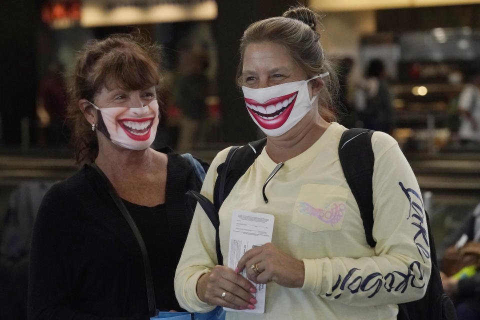 United Airlines passengers Michelle Fehr, left, and Susanne Bartley are interviewed as they wait to board a flight to Hawaii at San Francisco International Airport in San Francisco, Thursday, Oct. 15, 2020. Coronavirus weary residents and struggling business owners in Hawaii will be watching closely as tourists begin to return to the islands on Thursday without having to self-quarantine upon arrival. (AP Photo/Jeff Chiu)