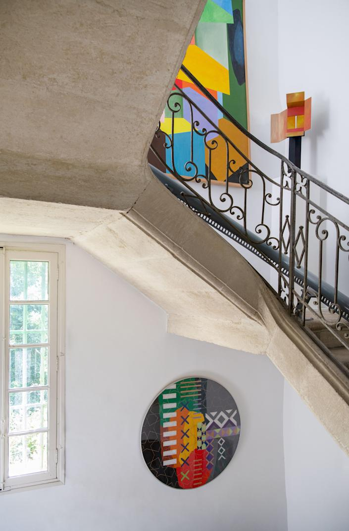 Artworks are displayed along the staircase.