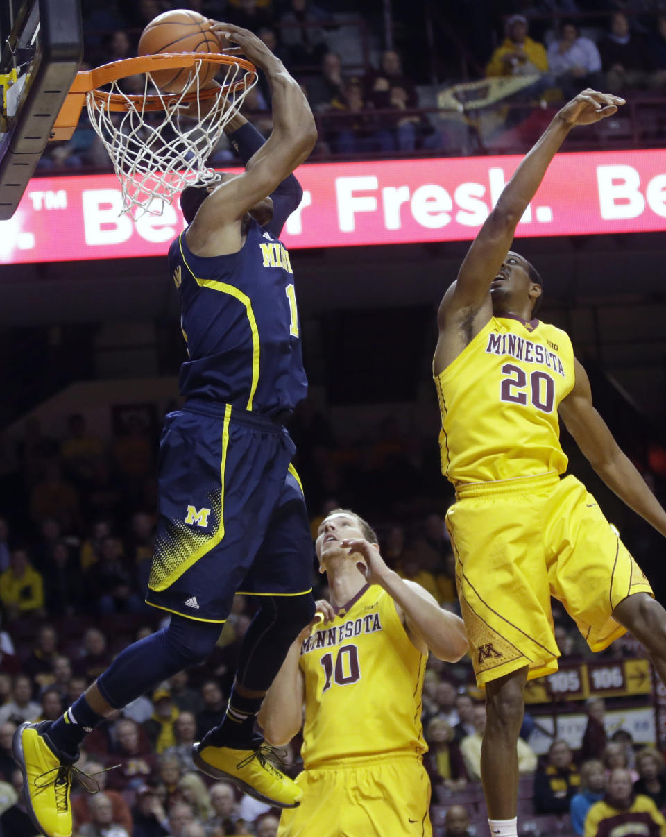 Michigan's Glenn Robinson III, left, does a reverse dunk as Minnesota's Oto Osenieks (10) and Austin Hollins defend during the first half of an NCAA college basketball game Thursday, Jan. 2, 2014, in Minneapolis. (AP Photo/Jim Mone)
