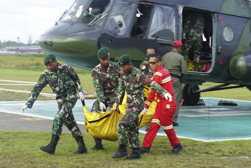 Indonesian soldiers carry a body bag containing the body of a victim of separatist attack in Nduga district upon its arrival at Moses Kilangin Airport in Timika, Papua province, Indonesia, Friday, Dec. 7, 2018. Army helicopters on Friday transported bodies of the victims who were killed in one of the bloodiest separatist attacks in Indonesia's restive Papua province. (AP Photo/Mujiono)