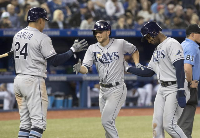 Tampa Bay Rays' Brandon Lowe, middle, is congratulated after scoring on his two-run home against the Toronto Blue Jays during the seventh inning of a baseball game Friday, April 12, 2019, in Toronto. (Fred Thornhill/The Canadian Press via AP)