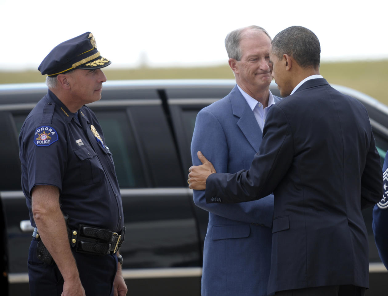 President Barack Obama greets Aurora (Colo.) Mayor Steve Hogan as Aurora Police Chief Daniel Oates, left, watches after Obama arrived at at Buckley Air Force Base, Colo., Sunday, July 22, 2012. (AP Photo/Susan Walsh)