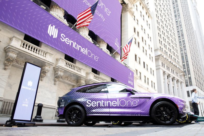 Signage and cars are displayed in honor of SentinelOne, a cybersecurity firm's IPO, outside the NYSE in New York