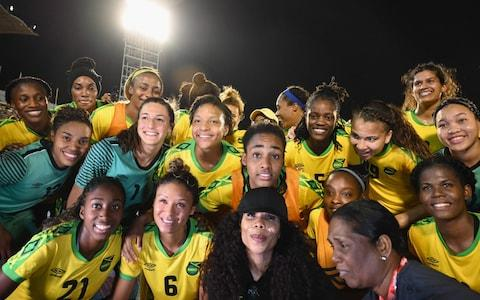 Cedella Marley (C bottom) poses with Jamaica Women's football team 'Reggae Girlz' after the friendly football match Jamaica vs Panama at the National Stadium in Kingston, Jamaica on May 19, 2019. - Credit: AFP
