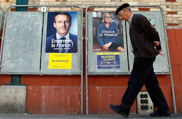 <p>A man walks past defaced election campaign posters for French centrist presidential candidate Emmanuel Macron and far-right candidate Marine Le Pen, in Saint Jean de Luz, southwestern France, Thursday, May 4, 2017. France will vote on Sunday May 7 in the second round of the presidential election. (AP Photo/Bob Edme) </p>