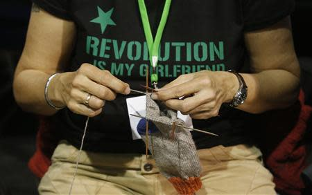 File photo of a member of Germany's environmental party Die Gruenen (The Greens) knitting a sock during a party congress in Berlin April 27, 2013. REUTERS/Tobias Schwarz/Files