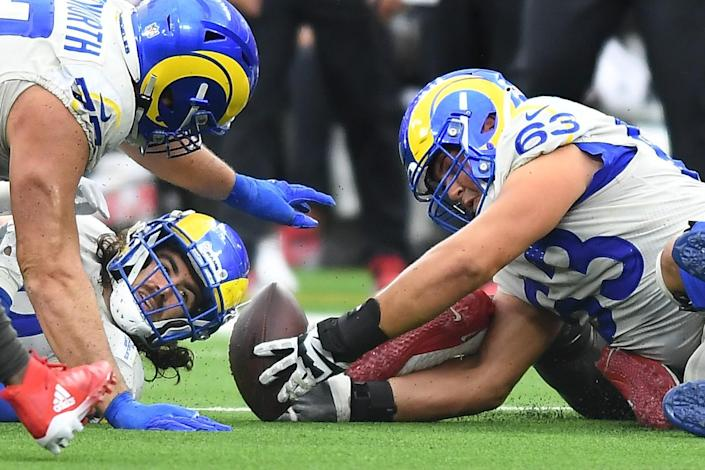 Rams tight end Tyler Higbee fumbles, but offensive linemen Rob Havenstein and Austin Corbett help recover the ball.